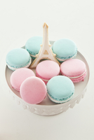 Pink and blue macarons on cake stand with Eiffel Tower cookie in the center, studio shot on white background