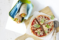 Homemade pizza on cutting board and healthy, vegetable sandwich wraps in container, studio shot on white background 11030048435| 写真素材・ストックフォト・画像・イラスト素材|アマナイメージズ