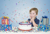 Young Boy with Birthday Presents and Making a Wish before Blowing Out Candles on Birthday Cake