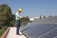 Maintenance worker stands with solar array on rooftop  Los 11044014101| 写真素材・ストックフォト・画像・イラスト素材|アマナイメージズ