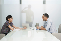 Man and woman talk over conference table man on mobile phone visible through translucent office wall 11044027652| 写真素材・ストックフォト・画像・イラスト素材|アマナイメージズ