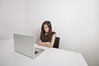 Angry young businesswoman with arms crossed looking at laptop in office 11044028441| 写真素材・ストックフォト・画像・イラスト素材|アマナイメージズ