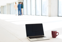 Laptop and coffee cup on floor with business people in background at new office 11044034901| 写真素材・ストックフォト・画像・イラスト素材|アマナイメージズ
