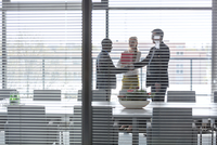 Businessmen shaking hands by female colleagues in board room seen through jalousie window 11044035036| 写真素材・ストックフォト・画像・イラスト素材|アマナイメージズ