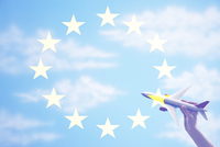 Person holding a toy plane flying in from of EU Flag 11044035671| 写真素材・ストックフォト・画像・イラスト素材|アマナイメージズ