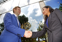 Low angle view of Multi ethnic business couple shaking hands 11044036051| 写真素材・ストックフォト・画像・イラスト素材|アマナイメージズ