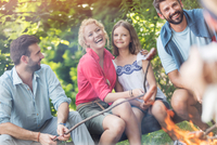 Tilt shot of happy family with male friend roasting sausages over campfire at park