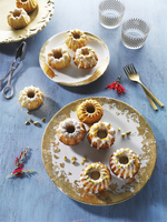 Mini Bundt cakes on gold-patterned plates on a blue wooden surface 11047048347| 写真素材・ストックフォト・画像・イラスト素材|アマナイメージズ