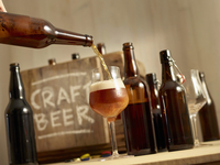 Beer being poured with open bottles of beer and a wooden crate labelled 'Craft Beer' in the background 11047048805| 写真素材・ストックフォト・画像・イラスト素材|アマナイメージズ