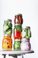 Preserving jars of freshly pickled vegetables stacked on an old stool 11047056018| 写真素材・ストックフォト・画像・イラスト素材|アマナイメージズ