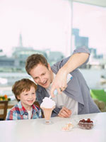 Father spraying whipped cream onto ice cream for son
