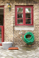 Brush and garden hose against brick wall