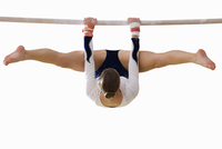 Female gymnast performing on bar, cut out