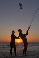 Young couple kiteboarding on beach at sunset, woman supporting man, side view (silhouette) 11080009483| 写真素材・ストックフォト・画像・イラスト素材|アマナイメージズ