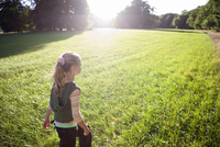 Blonde girl (7-9) walking in field in bright sunlight, rear view, trees in background (lens flare) 11080009525| 写真素材・ストックフォト・画像・イラスト素材|アマナイメージズ