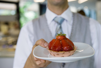 Waiter serving strawberry tart dessert in cafe, close-up, front view, focus on foreground 11080009607| 写真素材・ストックフォト・画像・イラスト素材|アマナイメージズ