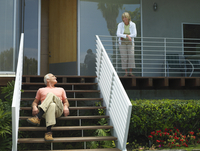 Senior couple relaxing at home, woman standing on veranda, man sitting on steps, smiling 11080009694| 写真素材・ストックフォト・画像・イラスト素材|アマナイメージズ