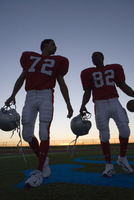 Two American football players leaving pitch at sunset, side by side, front view (surface level, backlit) 11080009816| 写真素材・ストックフォト・画像・イラスト素材|アマナイメージズ