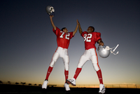 Two American football players celebrating on pitch at sunset, jumping up, doing high-fives, low angle view (backlit) 11080009817| 写真素材・ストックフォト・画像・イラスト素材|アマナイメージズ