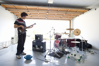 Teenage boy (16-18) playing electric guitar in garage by drum kit, side view