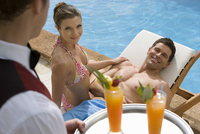 Waiter serving tropical drinks to couple sitting at poolside 11080010955| 写真素材・ストックフォト・画像・イラスト素材|アマナイメージズ