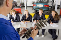 Teacher with auto part teaching students automotive trade in vocational school 11080011473| 写真素材・ストックフォト・画像・イラスト素材|アマナイメージズ