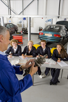 Teacher with auto part teaching students automotive trade in vocational school 11080011474| 写真素材・ストックフォト・画像・イラスト素材|アマナイメージズ