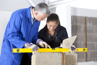 Teacher talking to student using level in bricklaying vocational school 11080011531| 写真素材・ストックフォト・画像・イラスト素材|アマナイメージズ