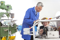 Teacher helping student constructing electric vehicle prototype in vocational school 11080011540| 写真素材・ストックフォト・画像・イラスト素材|アマナイメージズ