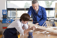 Teacher and student in woodworking class working on model airplane together 11080011735| 写真素材・ストックフォト・画像・イラスト素材|アマナイメージズ