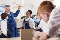 Teacher explaining wooden model airplane to students in vocational classroom 11080011748| 写真素材・ストックフォト・画像・イラスト素材|アマナイメージズ