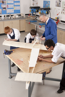 Teacher and students working on large wooden model airplane in woodworking class 11080011749| 写真素材・ストックフォト・画像・イラスト素材|アマナイメージズ