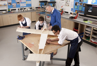 Teacher and students working on large wooden model airplane in woodworking class 11080011750| 写真素材・ストックフォト・画像・イラスト素材|アマナイメージズ