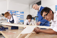 Teacher and students working on large wooden model airplane in woodworking class 11080011751| 写真素材・ストックフォト・画像・イラスト素材|アマナイメージズ