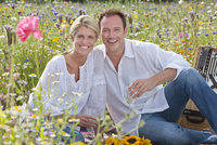 Portrait of smiling couple drinking white wine and picnicking in sunny wildflower field 11080012167| 写真素材・ストックフォト・画像・イラスト素材|アマナイメージズ