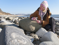 Woman looking at fossil in rock on ocean beach in winter 11080012229| 写真素材・ストックフォト・画像・イラスト素材|アマナイメージズ