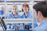 Portrait of smiling supervisor and technician assembling circuit board in manufacturing plant 11080012835| 写真素材・ストックフォト・画像・イラスト素材|アマナイメージズ