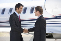 Two business colleagues shaking hands before departure 11080014322| 写真素材・ストックフォト・画像・イラスト素材|アマナイメージズ