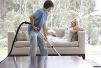 A young boy vacuuming whilst his mother relaxes 11080014983| 写真素材・ストックフォト・画像・イラスト素材|アマナイメージズ