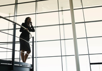 A businesswoman talking on a mobile phone in a modern office building 11080015940| 写真素材・ストックフォト・画像・イラスト素材|アマナイメージズ