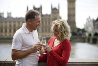 A middle-aged couple in front of the Houses of Parliament, toasting with champagne