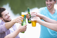 Young Couples Making A Toast With Beer Standing By River 11080019860| 写真素材・ストックフォト・画像・イラスト素材|アマナイメージズ