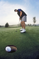 Low angle view of a man putting his ball into the hole on a golf course 11080022379| 写真素材・ストックフォト・画像・イラスト素材|アマナイメージズ
