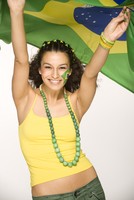 Hispanic woman cheering with Brazilian flag
