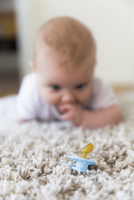 Baby girl looking at pacifier on rug 11081004830| 写真素材・ストックフォト・画像・イラスト素材|アマナイメージズ