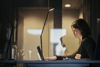 Side view of businesswoman using laptop at desk in dark office
