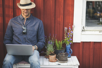 Man using laptop while sitting on bench by potted plants in back yard 11081014314| 写真素材・ストックフォト・画像・イラスト素材|アマナイメージズ