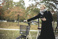 Smiling businesswoman enjoying music while walking with bicycle during autumn 11081015274| 写真素材・ストックフォト・画像・イラスト素材|アマナイメージズ
