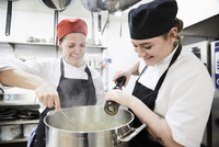 Teacher with female student adding pepper into cooking pan at commercial kitchen 11081015970| 写真素材・ストックフォト・画像・イラスト素材|アマナイメージズ