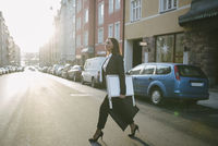 Side view of female realtor carrying signboard and bag while crossing street in city 11081016658| 写真素材・ストックフォト・画像・イラスト素材|アマナイメージズ